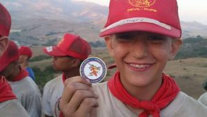 Another picture of A kid from the Devil Pups' program holding a patch