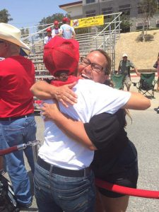 Maria, the founder of Youth Leadership Authority, hugging a Southern Nevada Devil Pups member