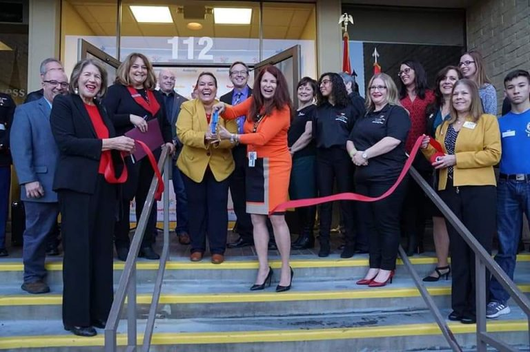Marie Tomao cutting a ribbon at a grand opening